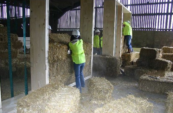 Straw being fitted into a prefab frame.
